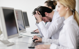 stressed out guy among coworkers at computers