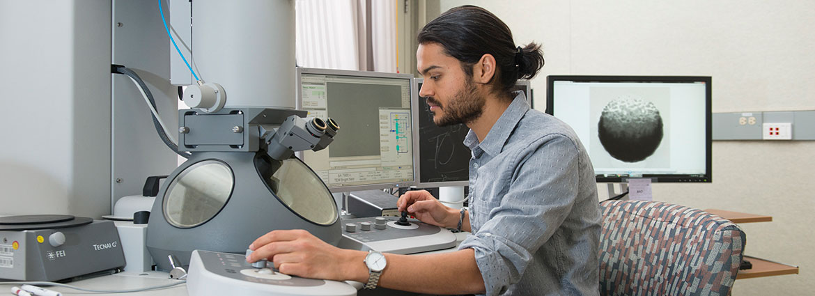 Graduate student using an electron microscope in a nanolab