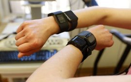 two arms with fitness trackers worn on wrists